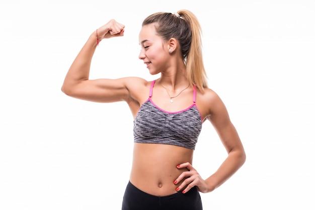 La giovane ragazza graziosa di forma fisica mostra il suo corpo forte del muscolo su bianco