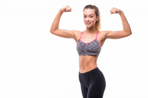 Young pretty fitness girl shows her strong fit body on white