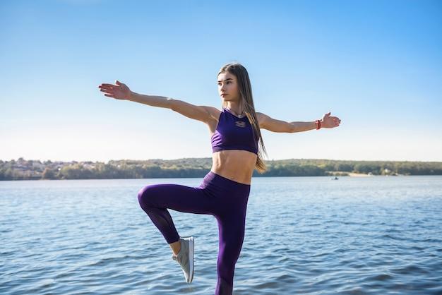 Молодая красивая женщина фитнеса делает позы йоги, растягивая в природе. здоровый образ жизни