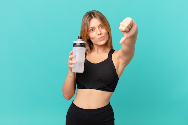 Young pretty fitness woman feeling cross,showing thumbs down