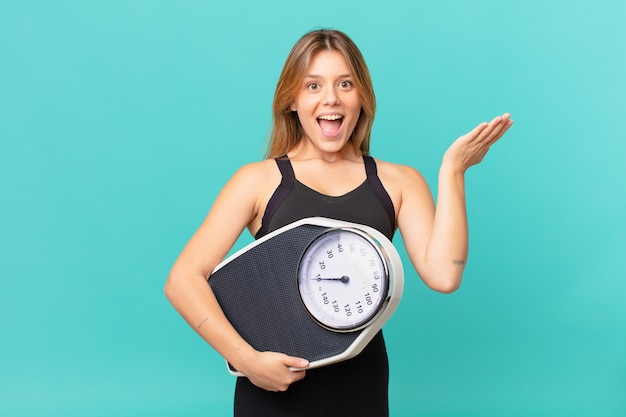 Young pretty fitness woman feeling happy and astonished at something unbelievable