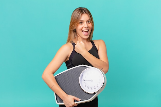 Young pretty fitness woman feeling happy and facing a challenge or celebrating