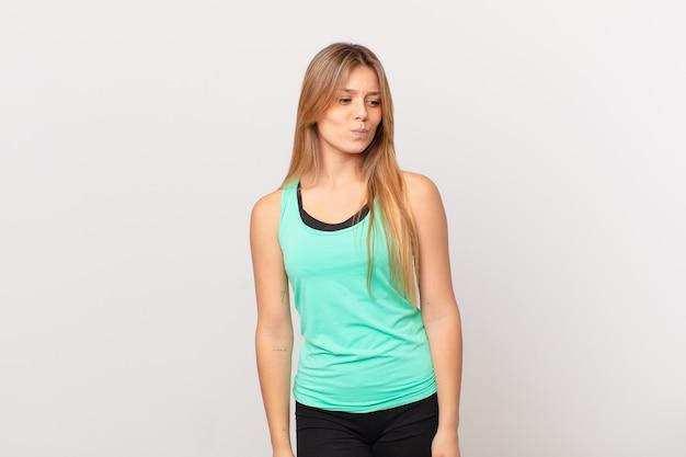 Молодая красивая фитнес-женщина грустит, расстроена или злится и смотрит в сторону