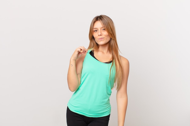 Young pretty fitness woman looking arrogant, successful, positive and proud
