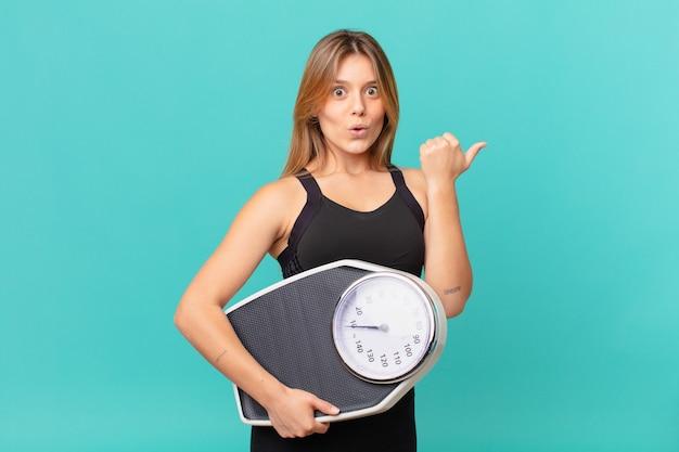 Молодая красивая фитнес-женщина выглядит удивленно в недоумении