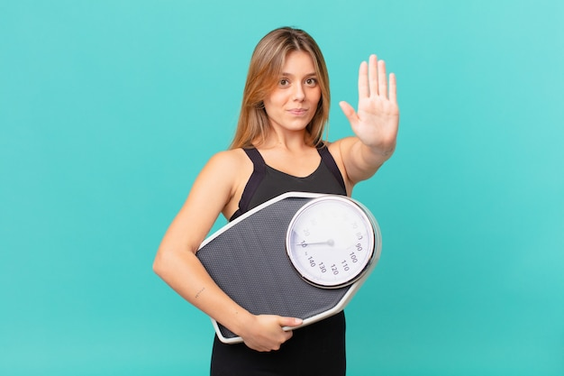 Young pretty fitness woman looking serious showing open palm making stop gesture