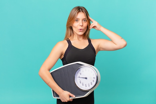 Young pretty fitness woman looking surprised, realizing a new thought, idea or concept