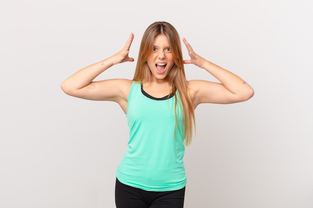 Young pretty fitness woman screaming with hands up in the air