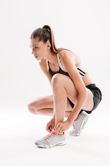 Young pretty fitness woman sitting and tying her shoelaces