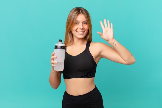 Молодая красивая женщина фитнеса улыбается и выглядит дружелюбно, показывая номер пять