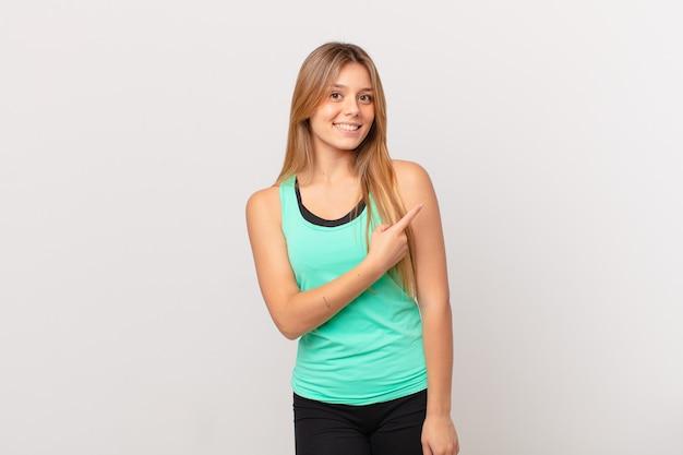 Молодая красивая женщина фитнеса весело улыбается, чувствует себя счастливой и указывая в сторону