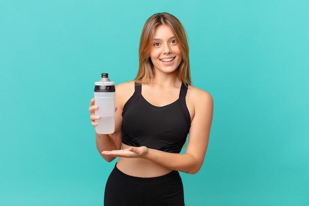 Молодая красивая женщина фитнеса весело улыбается, чувствует себя счастливой и показывает концепцию