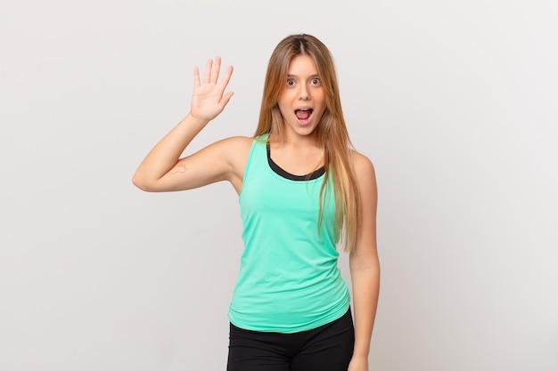 젊고 예쁜 피트니스 여성이 행복하게 웃고 손을 흔들며 환영하고 인사합니다.