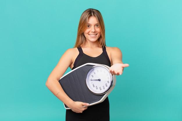 Молодая красивая женщина фитнеса счастливо улыбается с дружелюбием и предлагает и показывает концепцию