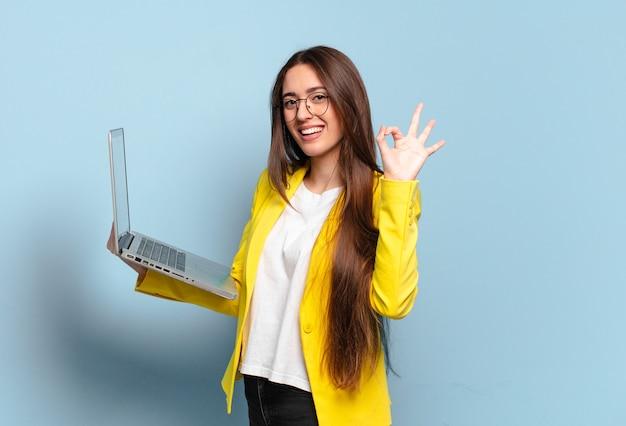 Молодая красивая женщина-фрилансер, держащая ноутбук