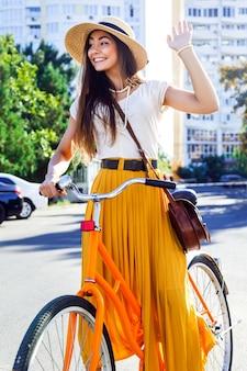 Giovane ragazza pazza abbastanza divertente che si diverte sulla bici hipster retrò al neon luminoso, indossa una maxi gonna vintage alla moda e un cappello di paglia, alza le mani in aria e saluta.