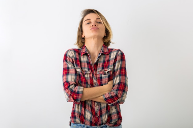 Young pretty funny emotional woman in checkered shirt posing isolated on white studio wall, showing angry gesture