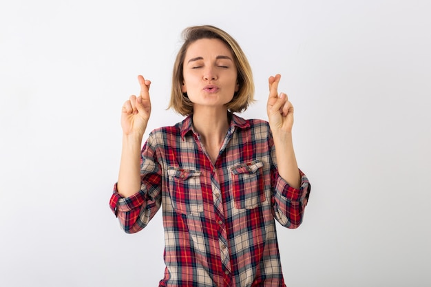 Young pretty funny emotional woman in checkered shirt posing isolated on white studio wall, showing lucky gesture