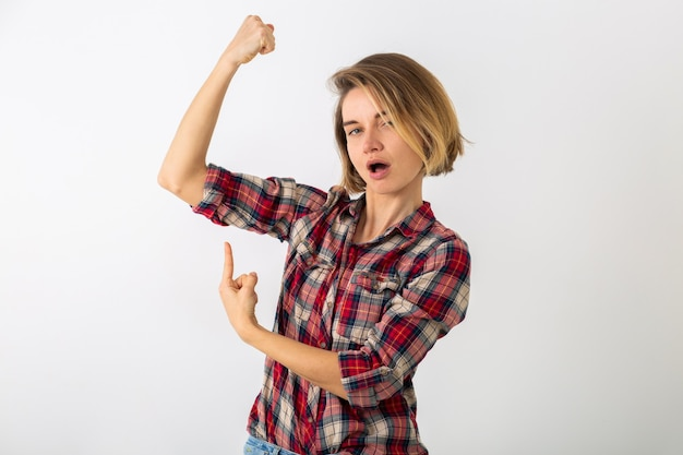 Young pretty funny emotional woman in checkered shirt posing isolated on white studio wall, showing strength gesture