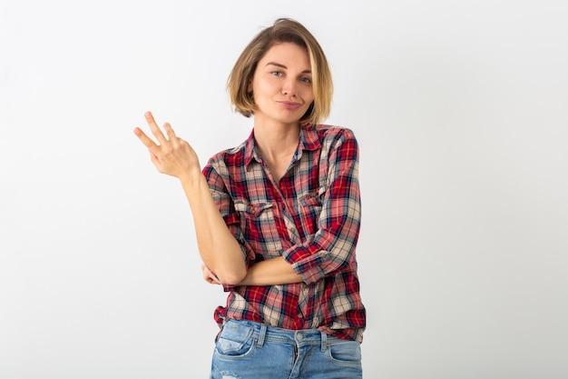 白いスタジオの壁に隔離され、ジェスチャーを示す市松模様のシャツのポーズで若いかなり面白い感情的な女性