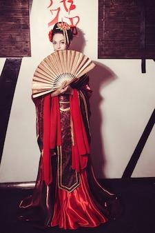 Молодая красивая гейша в кимоно с сакурой и украшениями