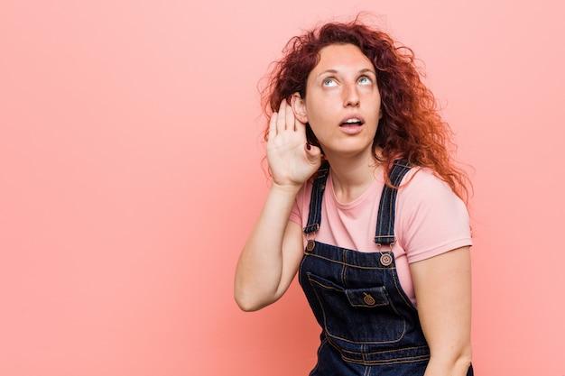 Молодая красивая рыжая рыжая женщина в джинсовых джинсах пытается слушать сплетни