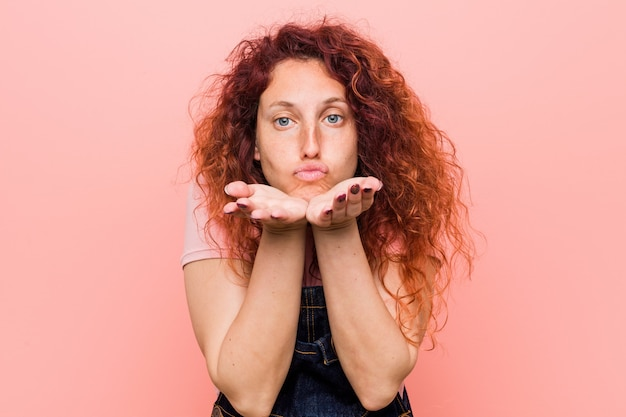 Young pretty ginger redhead woman wearing a jeans dungaree folding lips and holding palms to send air kiss.