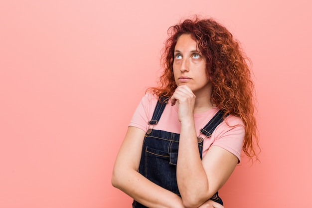 Young pretty ginger redhead woman wearing a jeans dungaree looking sideways with doubtful and skeptical expression.