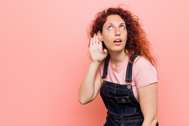 Young pretty ginger redhead woman wearing a jeans dungaree trying to listening a gossip