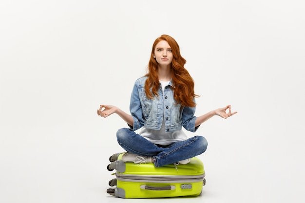 Young pretty ginger woman meditating in lotus pose on the luggage valise. isolated on white.
