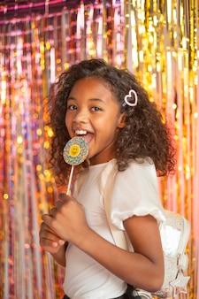 Молодая красивая девушка на праздничной вечеринке с леденцом на палочке