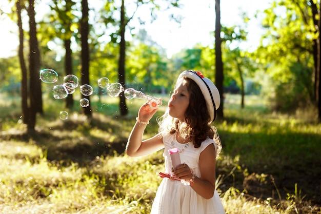 젊은 예쁜 여자 거품을 불고, 일몰 공원에서 산책.