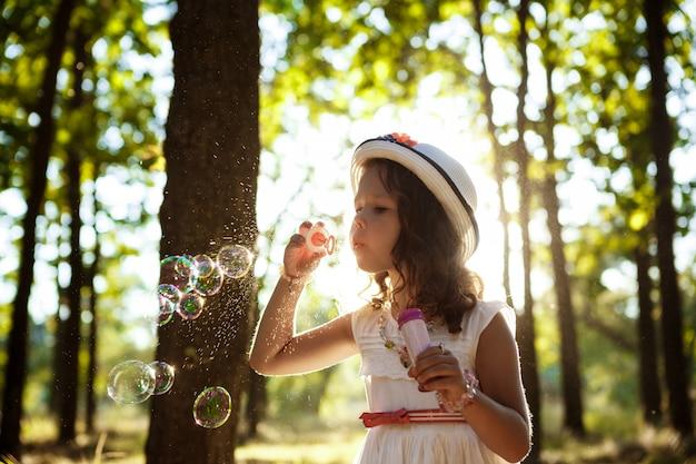 夕暮れ時の公園を歩いて、泡を吹いて若いきれいな女の子。