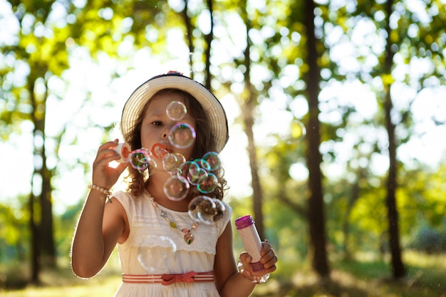 Молодая красивая девушка дует пузыри, прогулки в парке на закате.