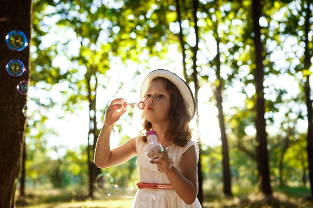 Young pretty girl blowing bubbles, walking in park at sunset.