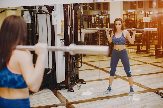 Giovane e bella ragazza in una tuta sportiva blu è impegnata nello sport in palestra