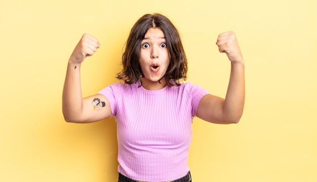 Молодая симпатичная девушка празднует невероятный успех как победительница, выглядит взволнованной и счастливой и говорит: «бери!»