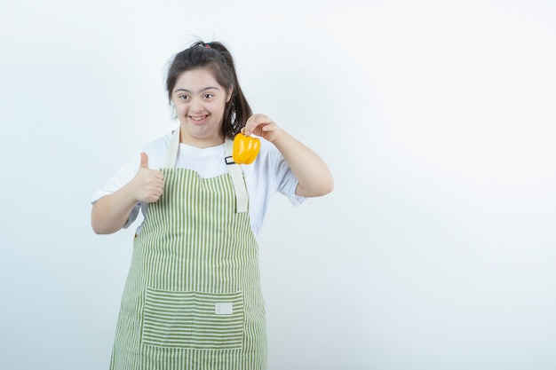 Young pretty girl in checkered apron holding yellow bell pepper and showing thumb up .