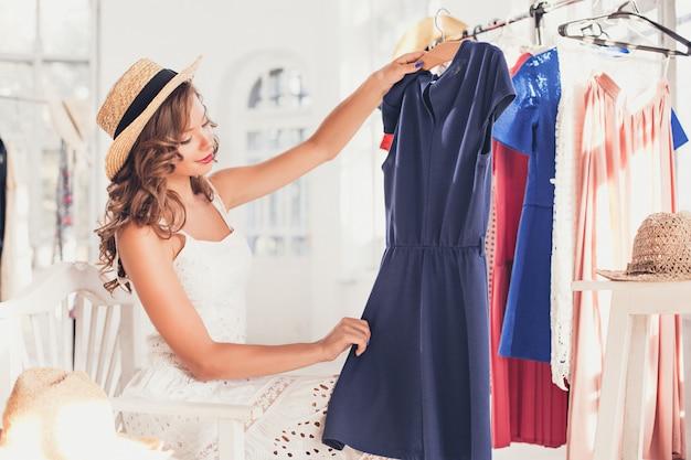 La giovane ragazza graziosa che sceglie e prova i vestiti al negozio