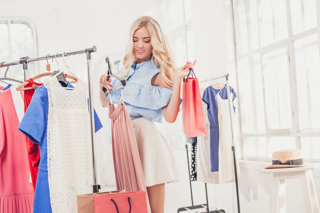 Young pretty girl choosing and trying on dresses at shop