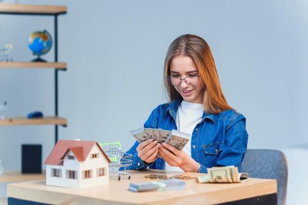 Молодая красивая девушка считает ее сбережения деньги и смотрит на модель дома.