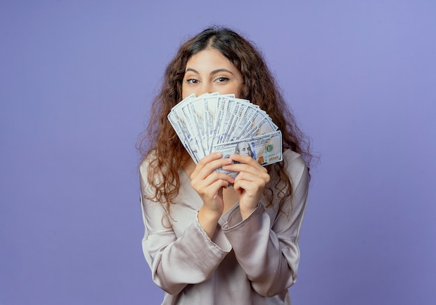 파란색 벽에 고립 된 돈으로 젊은 예쁜 여자 덮여 얼굴