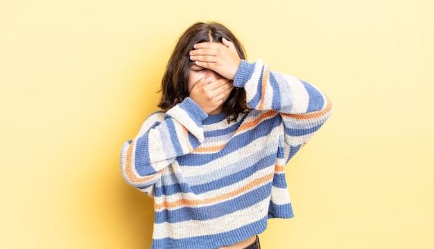 カメラにノーと言って両手で顔を覆っている若いかわいい女の子!写真を拒否したり、写真を禁止したりする
