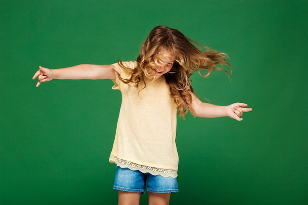 Young pretty girl dancing over green wall