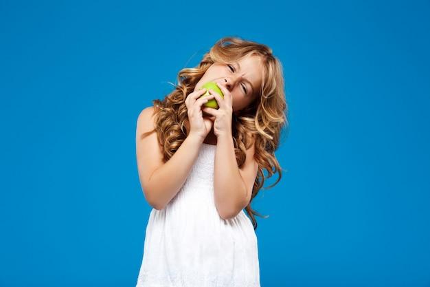 Молодая милая девушка есть зеленое яблоко над голубой стеной