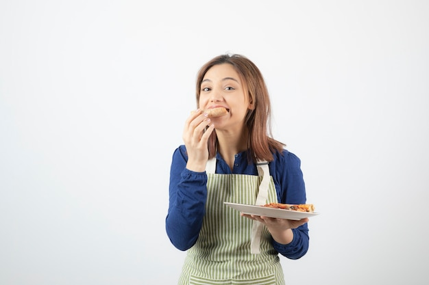 Giovane ragazza graziosa che mangia pizza su bianco.
