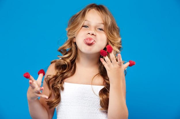 Молодая красивая девушка ест малину над синей стеной