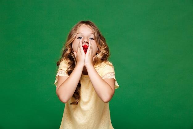 Молодая красивая девушка ест малину над зеленой стеной