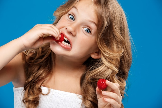Young pretty girl eating strawberry over blue wall