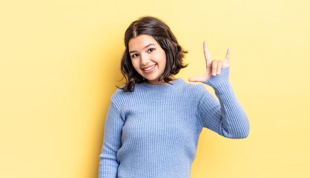 Молодая красивая девушка чувствует себя счастливой, веселой, уверенной, позитивной и мятежной, делая знак рок или хэви-метал рукой